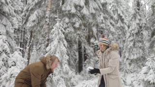 Young Happy Couple Playing in the Snow in the Winter Forest