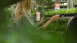 young woman chooses garden plants in the store