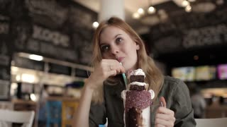 Young Woman Enjoys Drinks a Milkshake With a Brownie