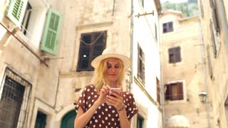 young woman in a summer dress with a smartphone in the old town