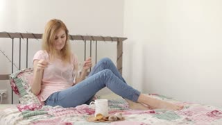 Young Woman Listening to Music With Headphones With Phone Sitting on the Bed