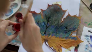 young woman paints a picture on a maple leaf