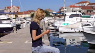 young woman with a phone sits on the pier with yachts