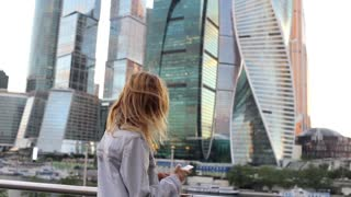 young woman with phone in the background of skyscrapers