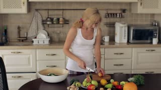 Woman Cuts Tomato For Salad