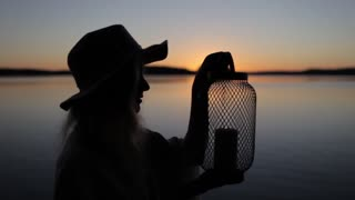 Woman Puts Out the Candle in the Lantern at Sunset by the Lake