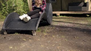 Woman Resting on a Lounger Beside a Tent in the Woods