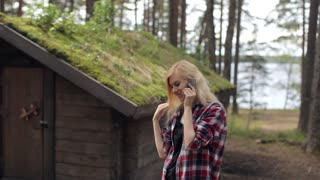 Woman Talking on the Phone Next to a Wooden House in the Woods