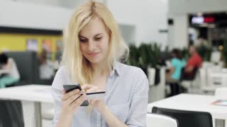 Woman Using Smartphone Online With Credit Card at Shopping Center