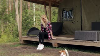 Woman With Dog Sitting in a Large Tent in the Woods