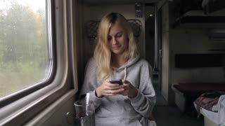 Woman Writes a Message on the Phone Sitting in a Train Window