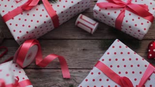 Women's Hands Lay Down a Holiday Gift Boxes on a Wooden Table