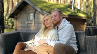 Young Couple Hugging Sitting on the Sofa at the Cabin in the Woods