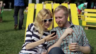 Young Couple Looking at Mobile Phone Sitting on a Lounger