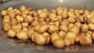 Young Potatoes Fried in Boiling Oil to a Large Frying Pan Over an Open Fire