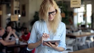 Young Woman Using Digital Tablet at Cafe