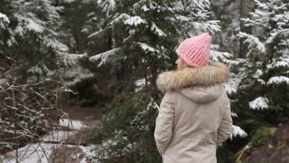 Young Woman Walking in a Forest Covered With Snow