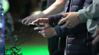 A lot of teenagers playing on gaming consoles. Close-up of hands with joypads.