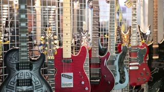 A lot of the coolest electric guitars on the stand in a music store.