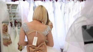 A young woman tries on a wedding dress Bridal salon. International Exhibition of Wedding Fashion Moscow.