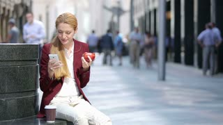Business lunch. A young attractive woman eating a red apple and use a smartphone on a city street.