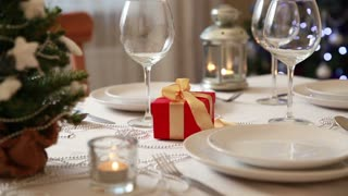 Christmas theme. Festive table setting with candles, gifts and Christmas lantern