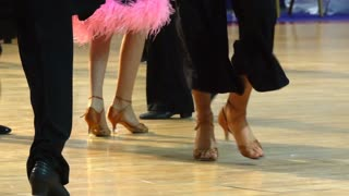Close-up of legs of dancing couples in ballroom. Slow motion.