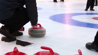 Curlers throw stones for curling on ice.