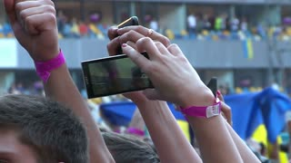 Fans waving their hands and hold phone with digital displays crowd at concert.