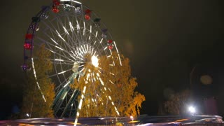 Ferris wheel in an amusement Park in festive lights in action. Time lapse.