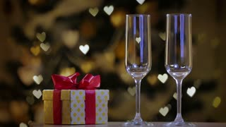 Glasses of champagne and a gold gift box with red ribbon on background of festive lights.