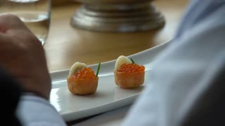 Gourmet eats tiny canapes with red caviar in the restaurant.