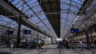 HELSINKI, FINLAND - MAY 24, 2016: Many passengers and trains at the railway station in Helsinki, Finland. Time Lapse. Zoom in.