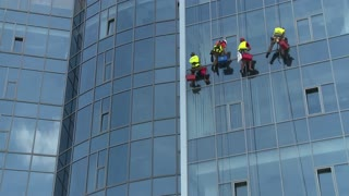 KIEV, UKRAINE - JUNE 15, 2014: Industrial Alpinists. Window washer on a skyscraper.