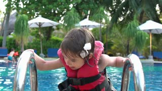 Little Girl In The Swimming Vest Floating In The Pool. Slow Motion.