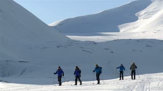 LONGYEARBYEN, SPITSBERGEN, NORWAY - APRIL 05, 2015: Group of tourists skiing in the far north, surrounded by the snow-covered hills.
