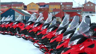 LONGYEARBYEN, SPITSBERGEN, NORWAY - APRIL 07, 2015: Bright red scooter on a background of a small town in the far north.
