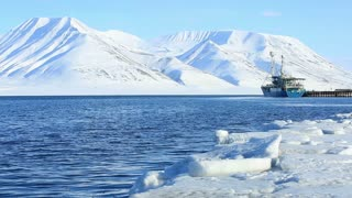 LONGYEARBYEN, SPITSBERGEN, NORWAY - APRIL 08, 2015: Cargo ship in a Norwegian port on the background of snowy mountains.