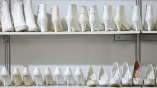 Lots of white wedding shoes on the shelves in the Bridal salon.
