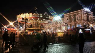 MOSCOW, RUSSIA - DECEMBER 15, 2014: A cheerful amusement park on Red Square on the eve of Christmas. Carousel rides, crowds and street vendors.