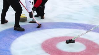 MOSCOW, RUSSIA - JANUARY 31, 2015: Players curling throw stones on the ice. The World Curling Tour in Moscow on Red Square