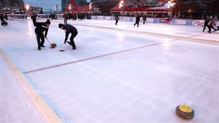 MOSCOW, RUSSIA - JANUARY 31, 2015: Players curling throw stones on the ice. The World Curling Tour in Moscow on Red Square.
