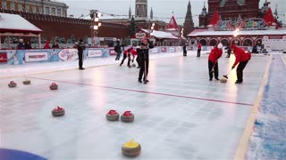 MOSCOW, RUSSIA - JANUARY 31, 2015: Players curling throw stones on the ice. The World Curling Tour in Moscow on Red Square.e.