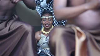"MOSCOW, RUSSIA - JUNE 06, 2015: Beautiful black young woman sits among men dancing during the International Festival of African culture ""AFROFEST."""