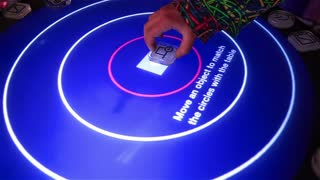"""MOSCOW, RUSSIA - OCTOBER 31, 2014: Musician uses reacTable - electroacoustic electronic musical instrument. The festival technologies, developments and achievements of mankind """"Days of the Future""""."""