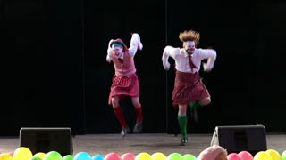 MOSCOW, RUSSIA - SEPTEMBER 12, 2015: Clowns in Scottish kilts dancing on stage. Festival of clown art Clownfest in Sokolniki Park.