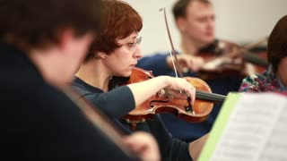 Orchestra rehearsal. Woman playing the violin. Bow string musical instruments.