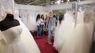 Shop assistant helps shoppers choose the wedding dress Bridal salon. International Exhibition of Wedding Fashion Moscow.