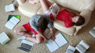 Students with books and laptop are learning at home