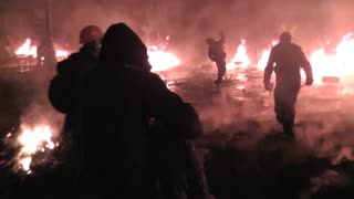 The streets of Kiev in the fire. Protesters throw stones and set fire to tyres on the barricade, the police use water cannons in January 2014.